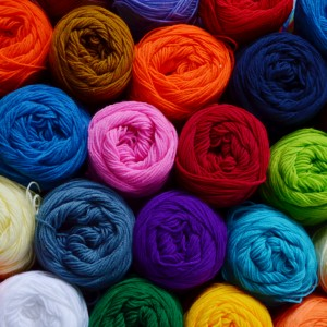 Blurry background of colorful yarn wool for knitting. View from above of colorful yarn wool for knitting.